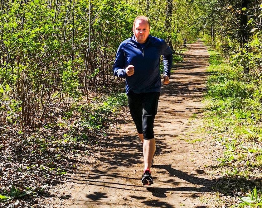 Mann joggt in Sportbekleidung auf Waldweg