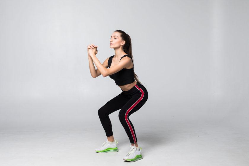 Junge Frau in Sportbekleidung führt gerade eine Kniebeuge durch.