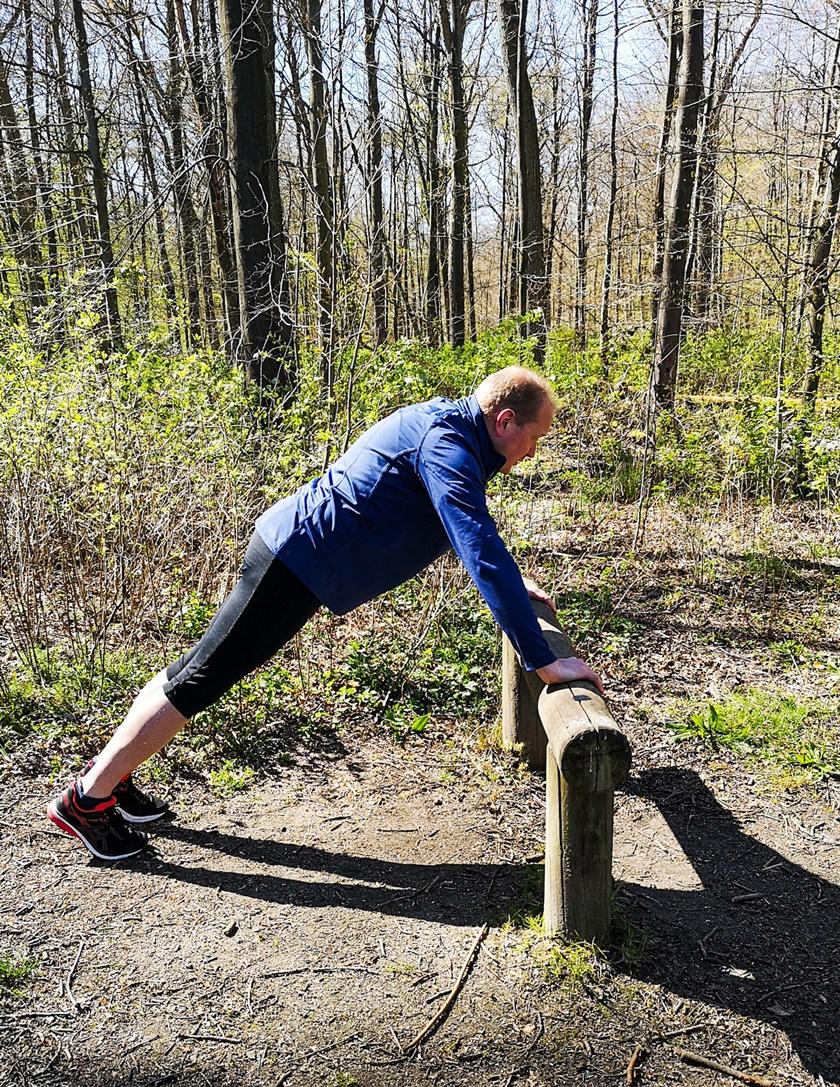 Mann in Sportbekleidung hat beim Liegestütz seinen gesamten Oberkörper nach oben gedrückt, und befindet sich in der Halteposition.