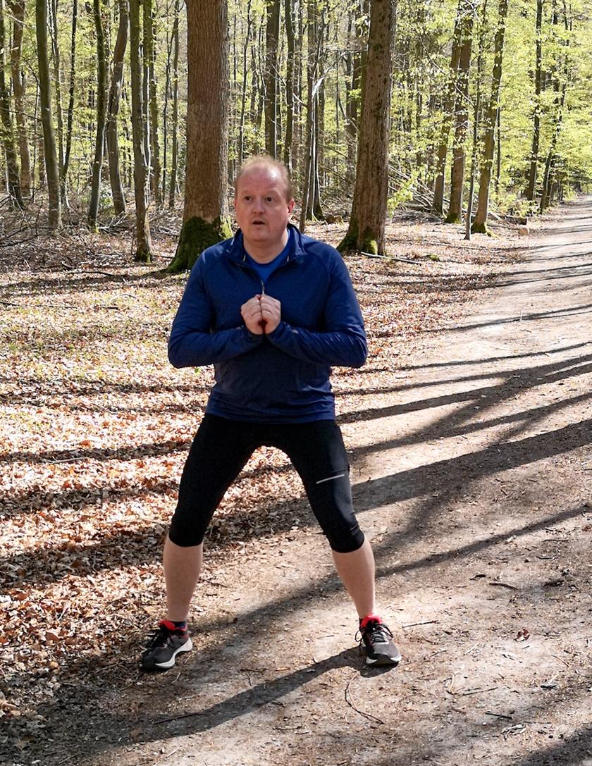 Mann in Sportbekleidung ist im Inbegriff den Ausfallschritt auszuführen und befindet sich in der Ausgangsposition.