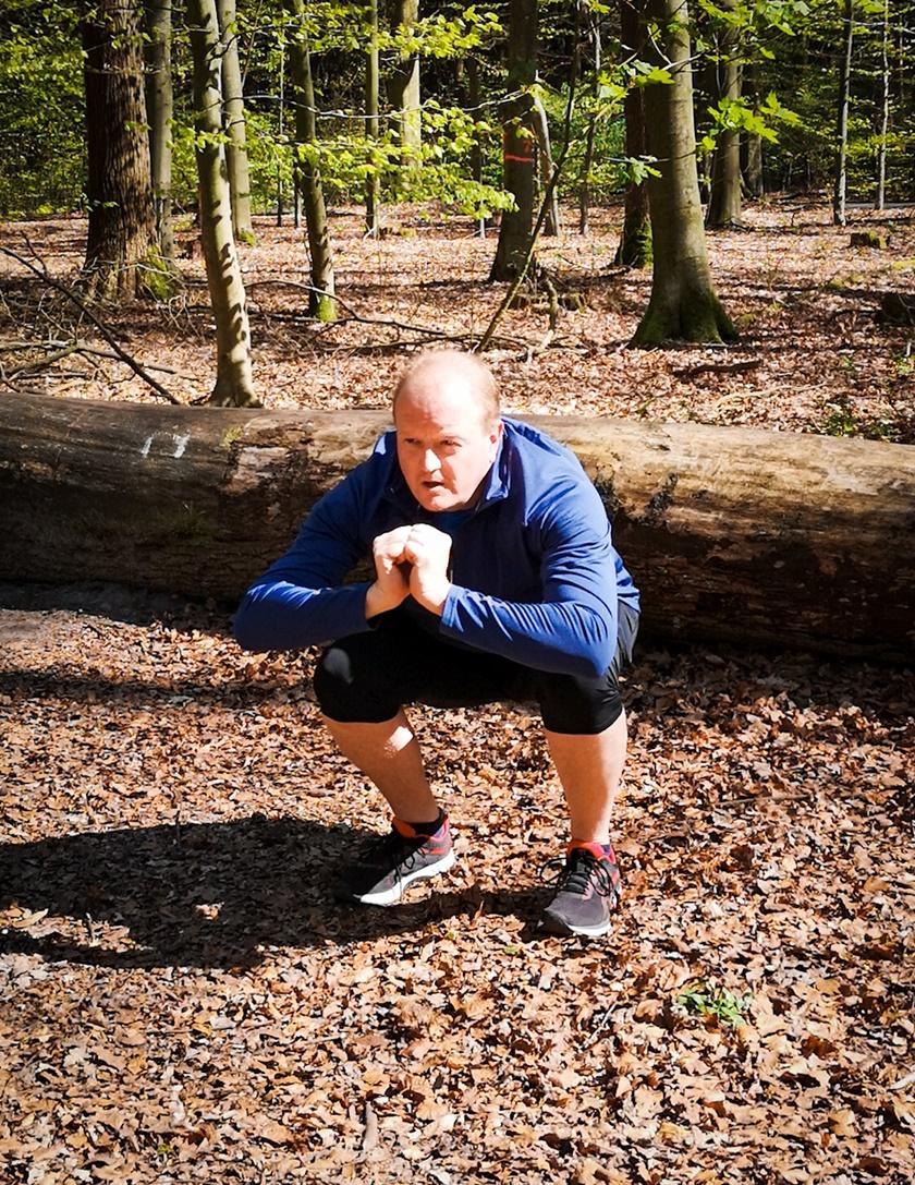 Mann in Sportbekleidung führt eine Kniebeuge durch und geht in die Hocke.