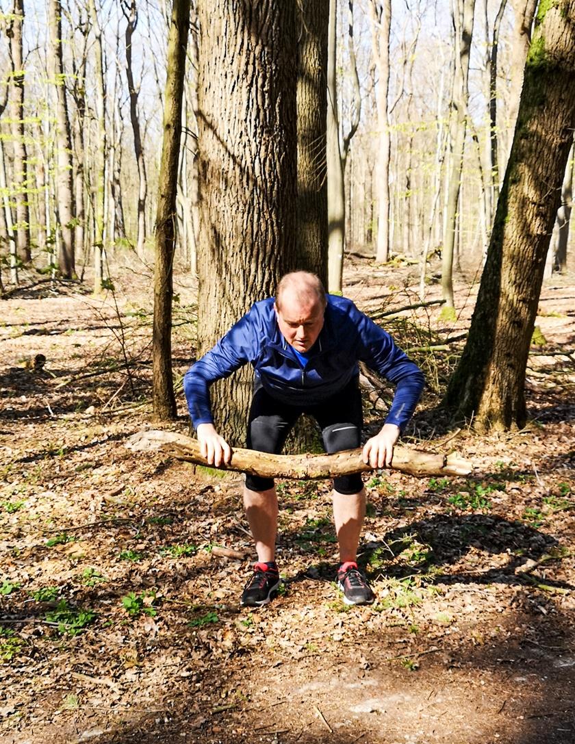 Mann in Sportbekleidung hebt einen Gegenstand beim Kreuzheben hoch und ist dabei in die gerade Rückenlage zu gehen.