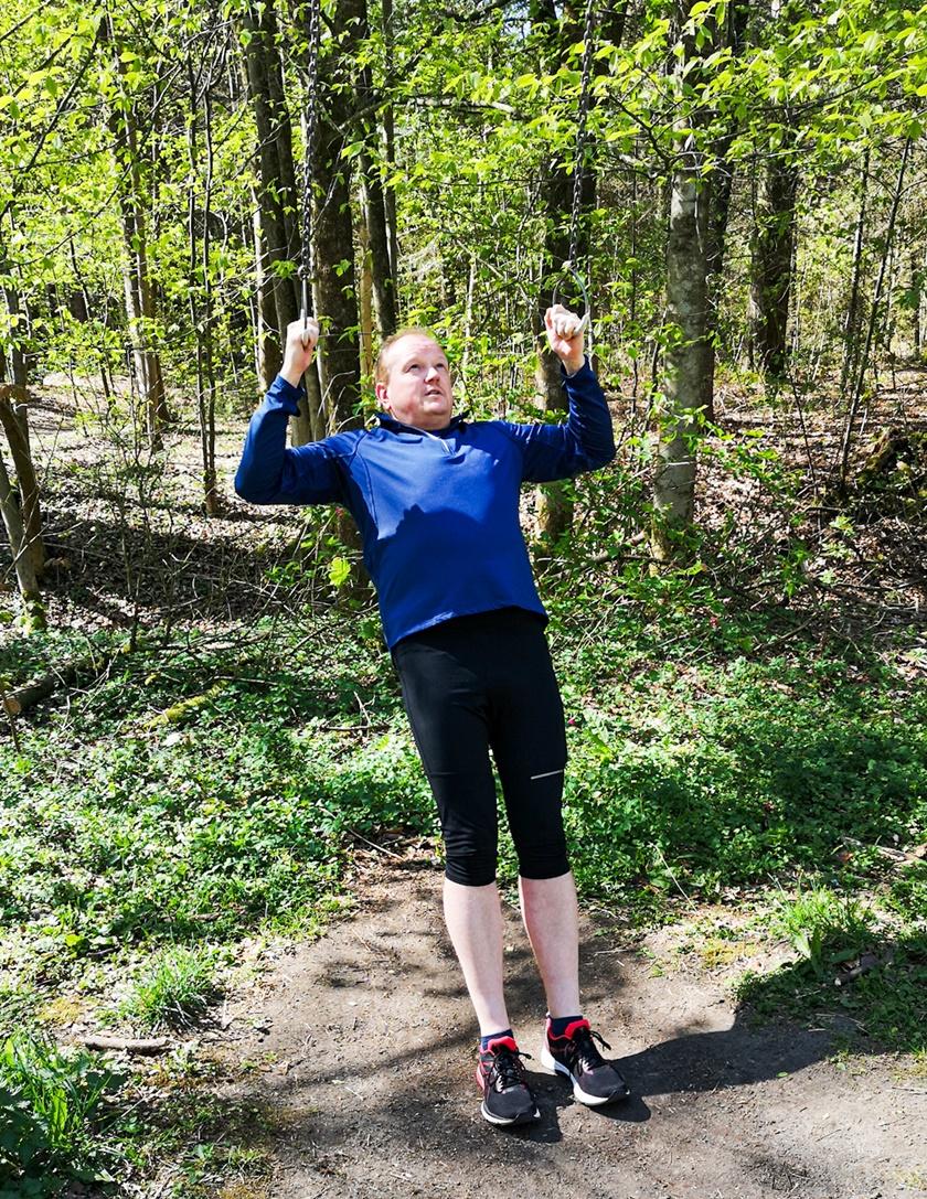Mann in Sportbekleidung hängt mit beiden Händen an einem Kettengeländer fest, in schräger Position, und hat gerade den Oberkörper hochgezogen.
