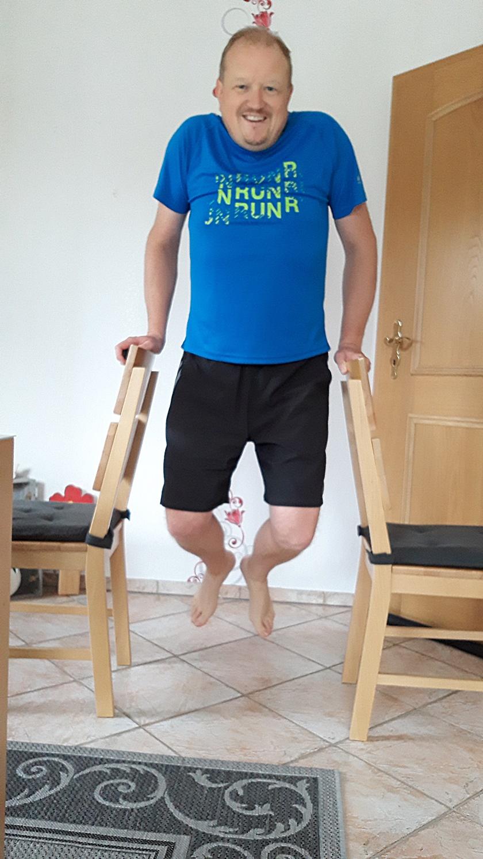 Mann im sportlichen Outfit führt einen Dip durch und hält sich an zwei Stuhllehnen fest.