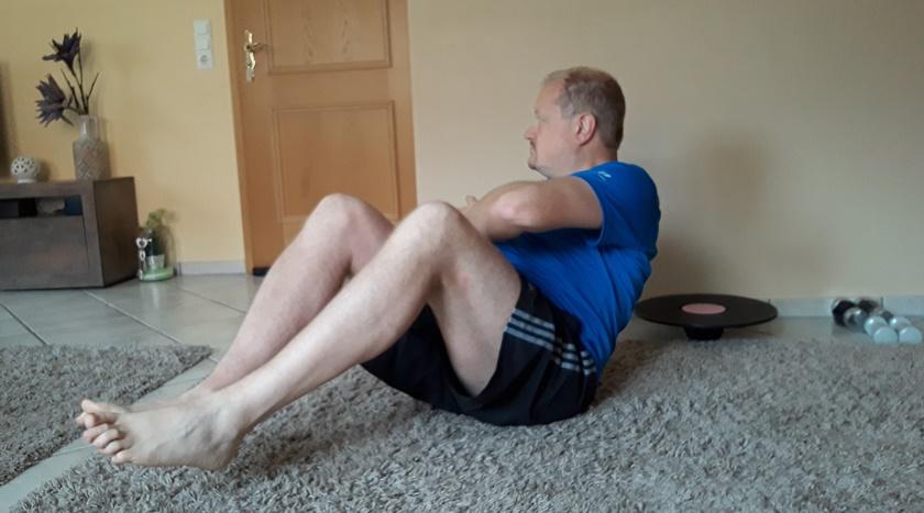 Ein Mann in Sportbekleidung ist dabei eine russische Drehung nach rechts in seinen eigenen 4 Wänden auszuführen.