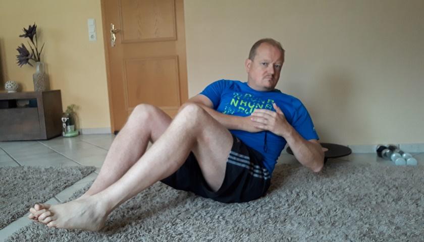 Ein Mann in Sportbekleidung führt gerade in seinem zuhause eine russische Drehung durch.