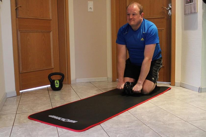 Ein Mann trainiert zuhause und befindet sich gerade beim Ausgangspunkt zum Training mit dem Ab Roller.