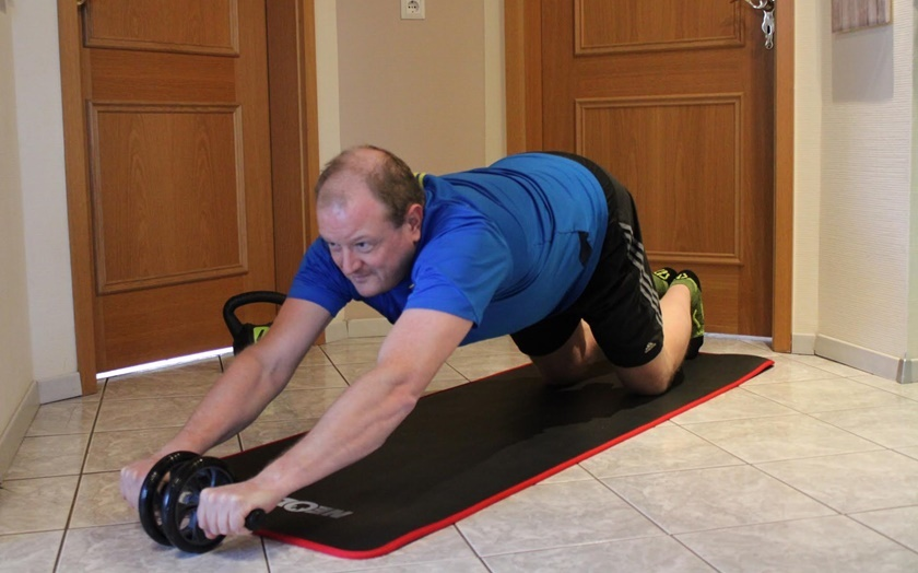 Mann in Sportbekleidung führt die Standardübung mit dem Bauchroller zu Ende.