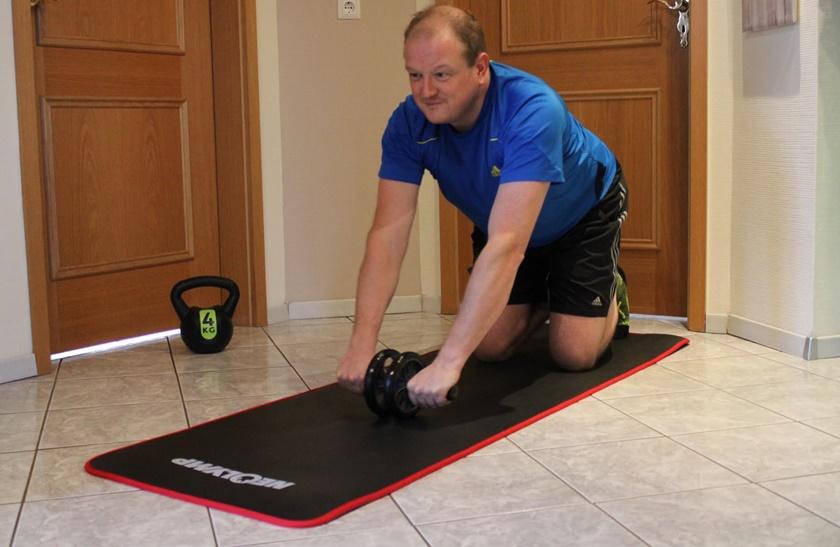 Mann in sportlichem Outfit führt gerade die Standardübung mit dem Bauchroller durch.