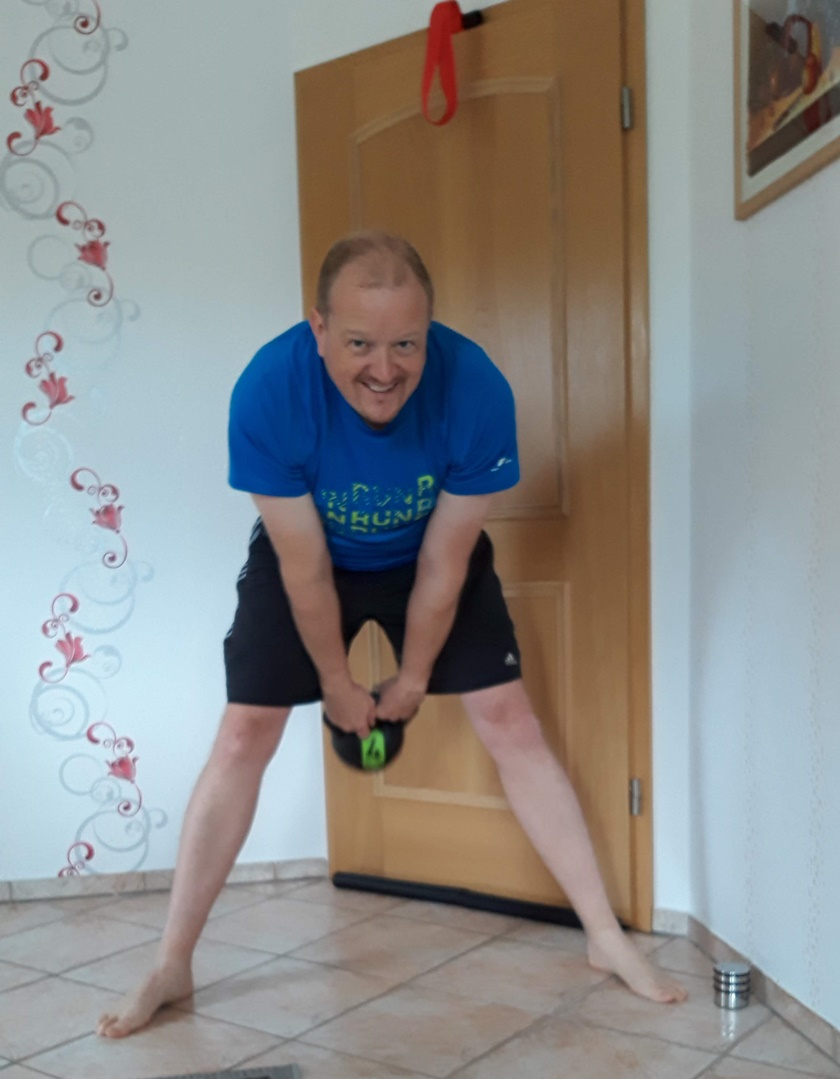 Mann im sportlichen Dress führt den Arm Swing mit dem Kettlebell durch, und schwingt durch die Beine hindurch.