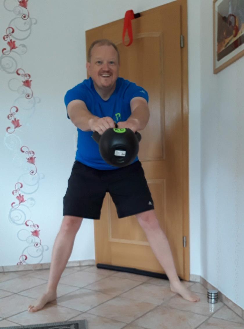 Mann in Sportbekleidung führt den Arm Swing mit dem Kettlebell durch und schwingt gerade nach vorne weg.