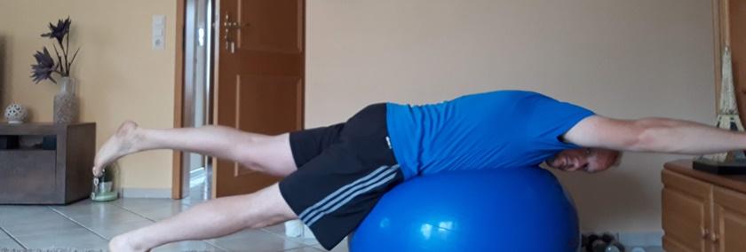 Mann in sportlichem Outfit führt gerade eine Bauchlage auf dem Pezziball durch.