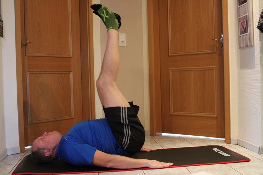 Mann in sportlicher Bekleidung hat das Beinheben vollzogen und hält einige Sekunden inne.