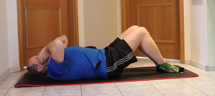 Mann der zuhause trainiert, ist dabei einen Crunch auszuführen, und befindet sich in der Ausgangsposition.