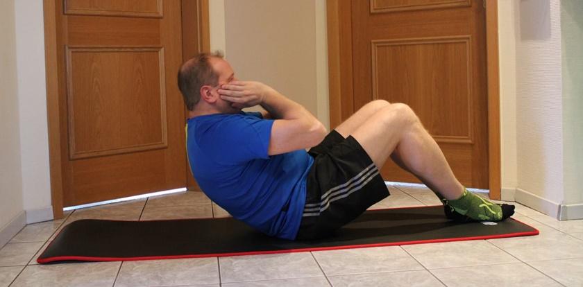 Ein Mann der zuhause trainiert, hat den Crunch derweil ausgeführt.