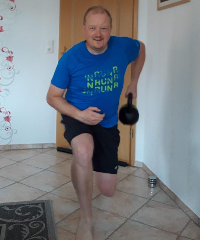 Mann im sportlichem Dress führt gerade das Rudern mit dem Kettlebell durch. Dabei bezieht er die Position des Ausfallschrittes.