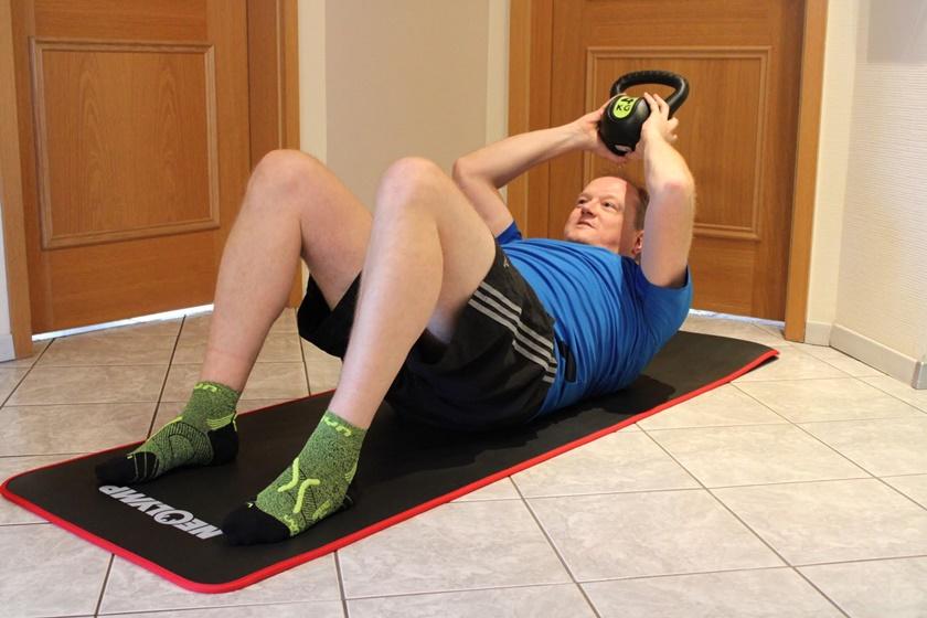 Mann in Sportbekleidung führt ein Sit Up aus mit dem Kettlebell. Hier bereits ausgeführt.