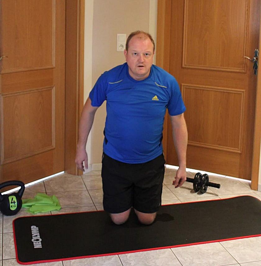 Mann im sportlichen Dress ist in der Ausgangspostion für den Squat Flow.