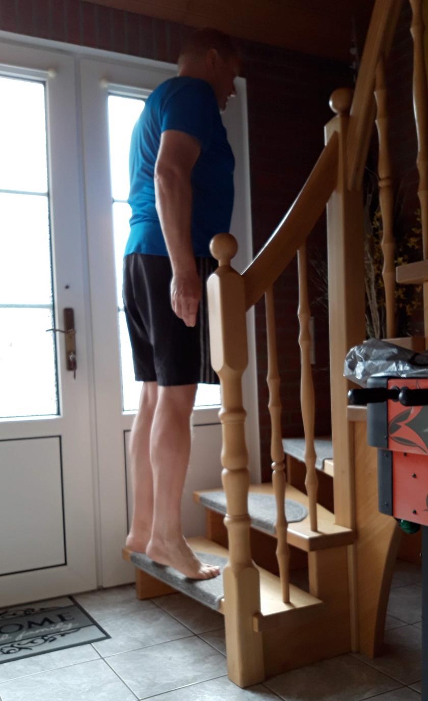 Mann in sportlichem Dress führt auf einer normalen Treppe das Wadenheben durch.
