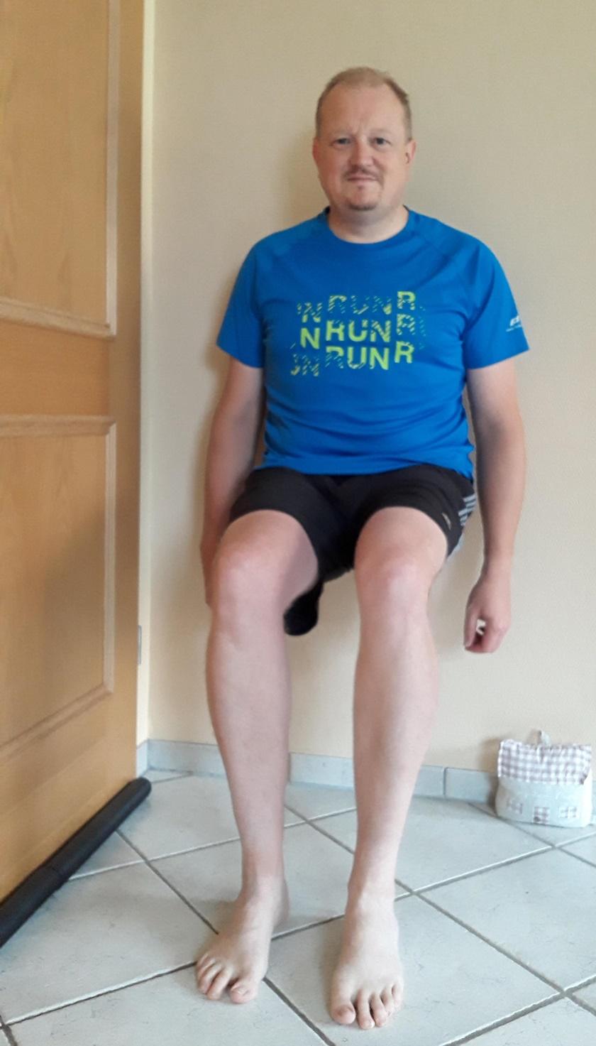 Mann im sportlichen Dress führt das Wandsitzen durch und verharrt mehrere Sekunden in diesem Zustand.