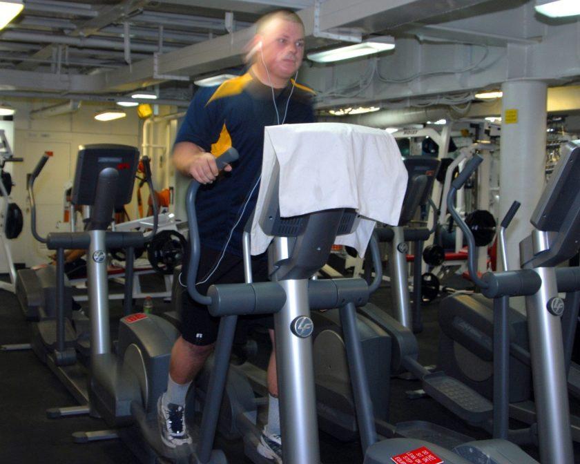 Ein Mann im Fitnessstudio trainiert mit dem Crosstrainer.