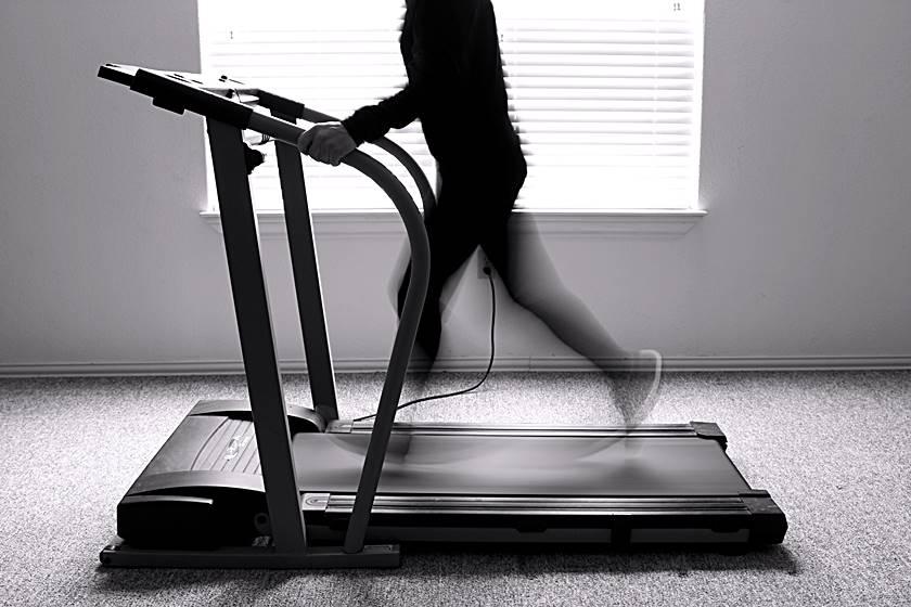 Schwarzweißbild mit einem Mann auf einem Laufband. Er trainiert gerade auf diesem Gerät.