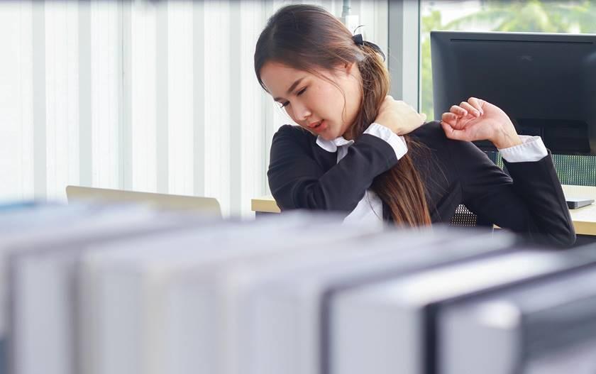 Eine Frau aus dem asiatischen Raum hat Nackenprobleme wegen ihrer Büroarbeit.
