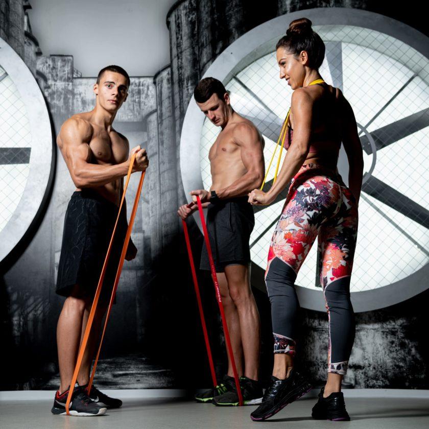 Eine Gruppe von Sportlern trainiert mit Widerstandsbändern. Sie führen verschiedene Übungen durch.
