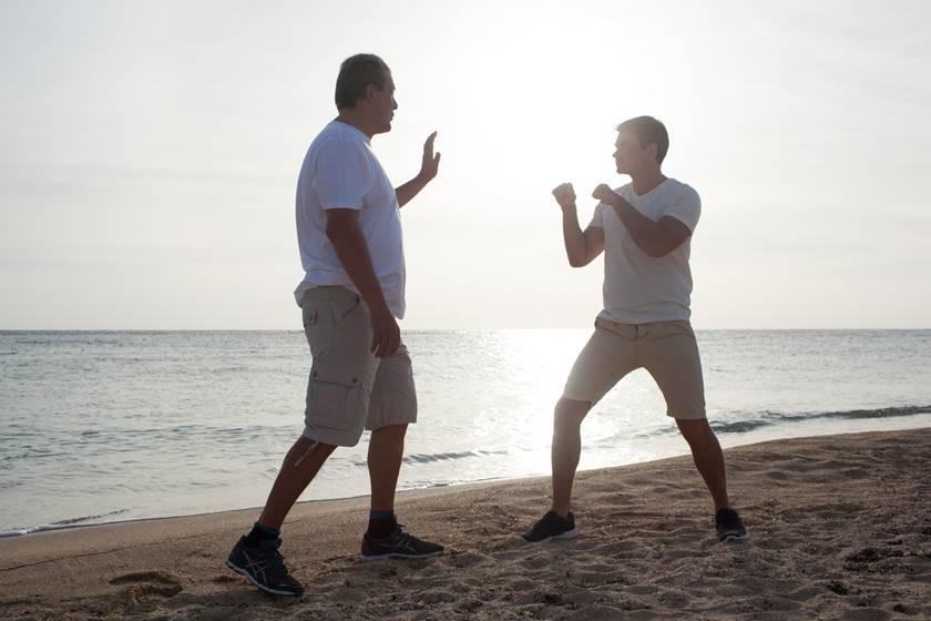 Zwei Männer stehen sich am Strand gegenüber und üben das Boxen