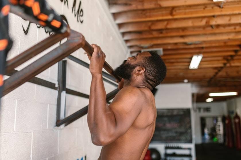 Ein Mann trainiert an einer Klimmzugstange Wand und hat den Klimmzug gerade vollendet.