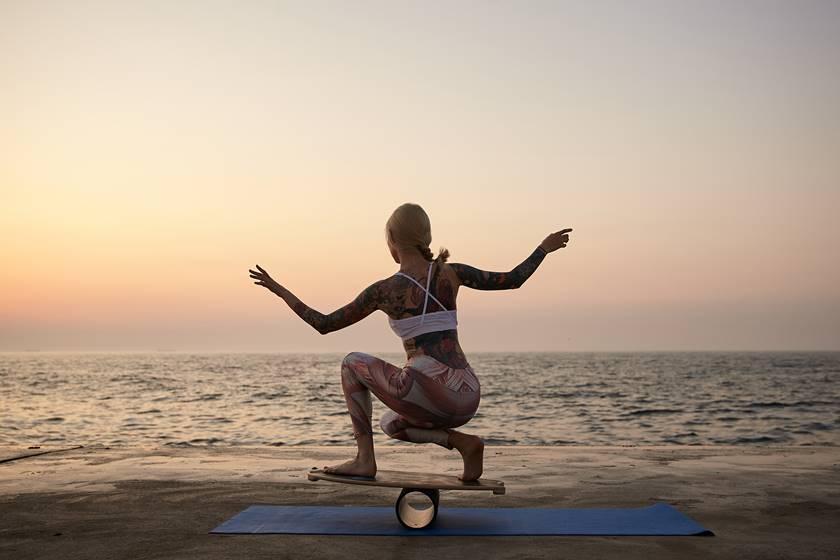 Eine Frau im sportlichen Dress übt an einem Strand mit dem Wackelbrett das Gleichgewicht zu halten.